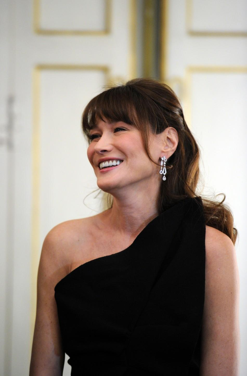French President Nicolas Sarkozy's wife Carla Bruni-Sarkozy welcomes guests prior to an official dinner at the Elysee Palace in Paris