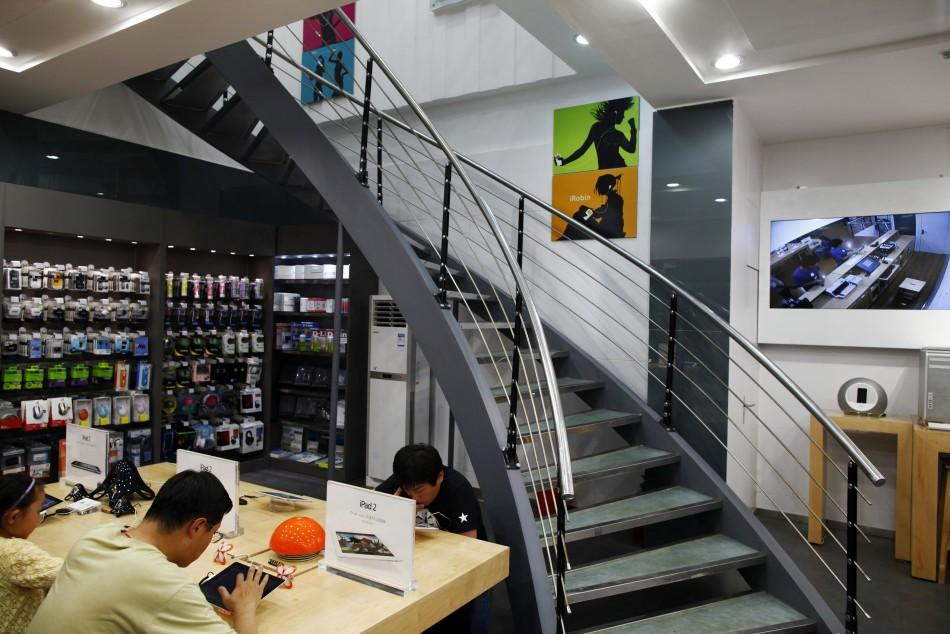 Customers test out electronic products in a fake Apple Store in Kunming, Yunnan province July 22, 2011.