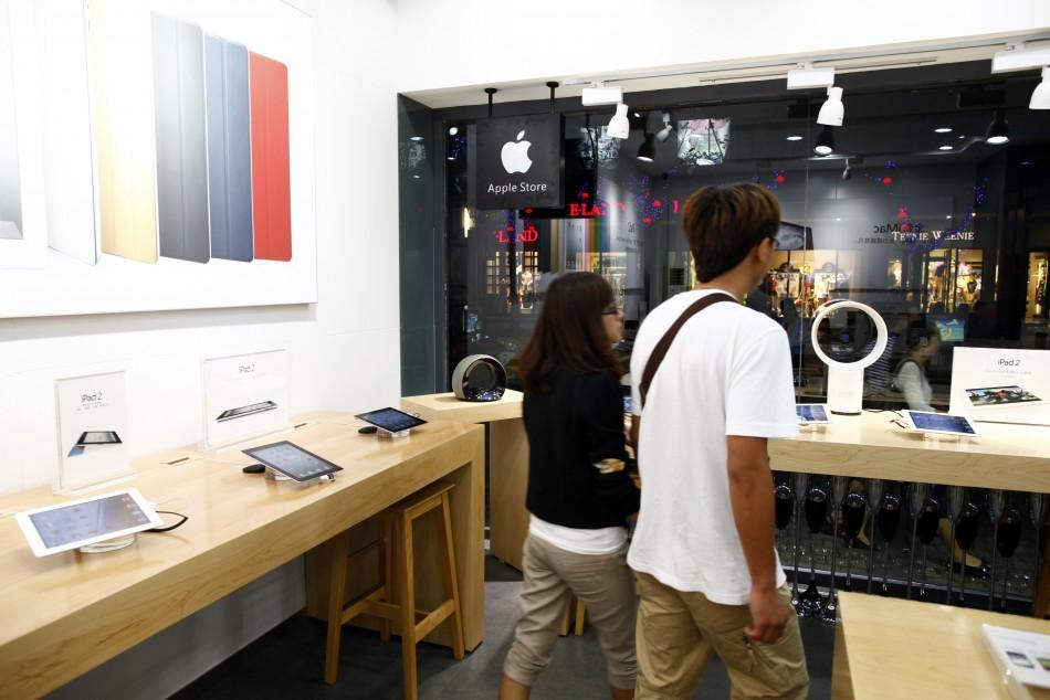 Customers walk past products in a fake Apple Store in Kunming, Yunnan province July 22, 2011.