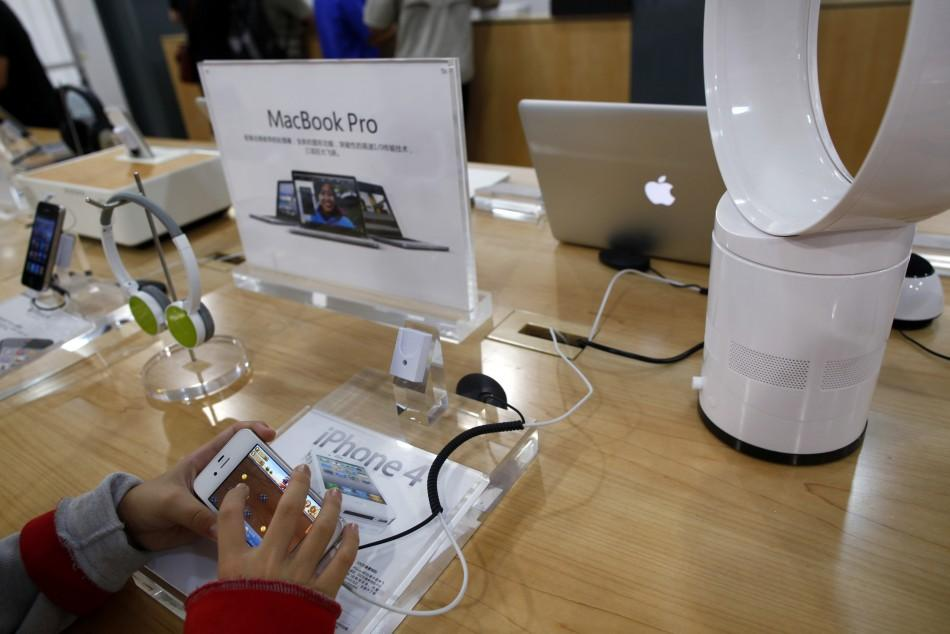 A boy plays with an iPhone 4 display set inside a fake Apple Store in Kunming, Yunnan province July 22, 2011.