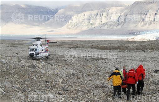 Rescuers carry one of the four youths injured in a polar bear attack on Spitsbergen island