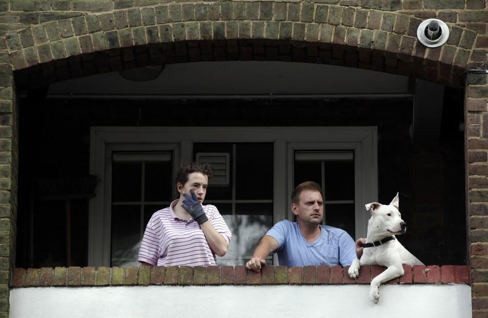 Residents of a housing estate watch as demonstrators march in north east London