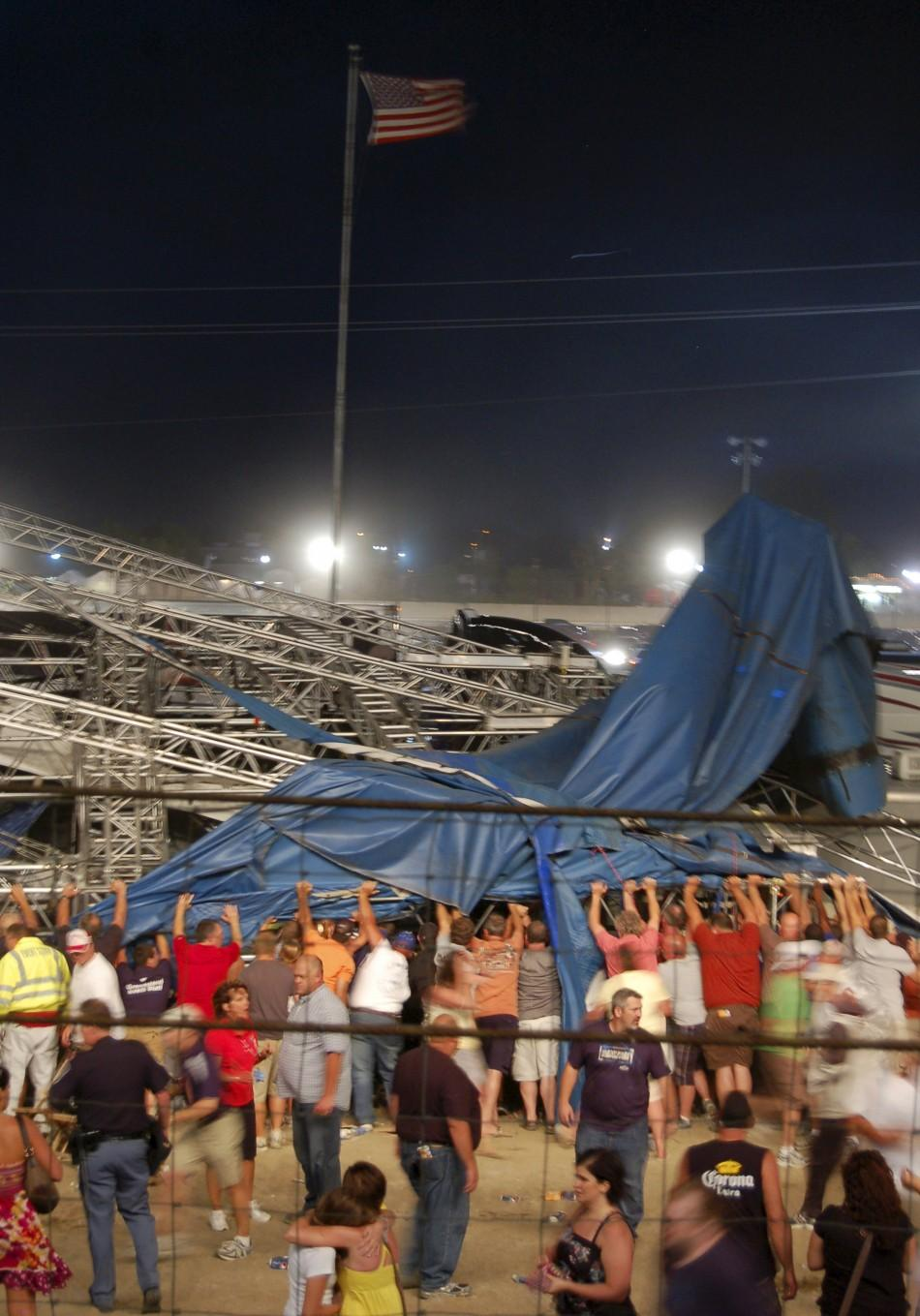 Concertgoers and emergency personnel hold up stage rigging after it collapsed at the Indiana State Fairgrounds in Indianapolis