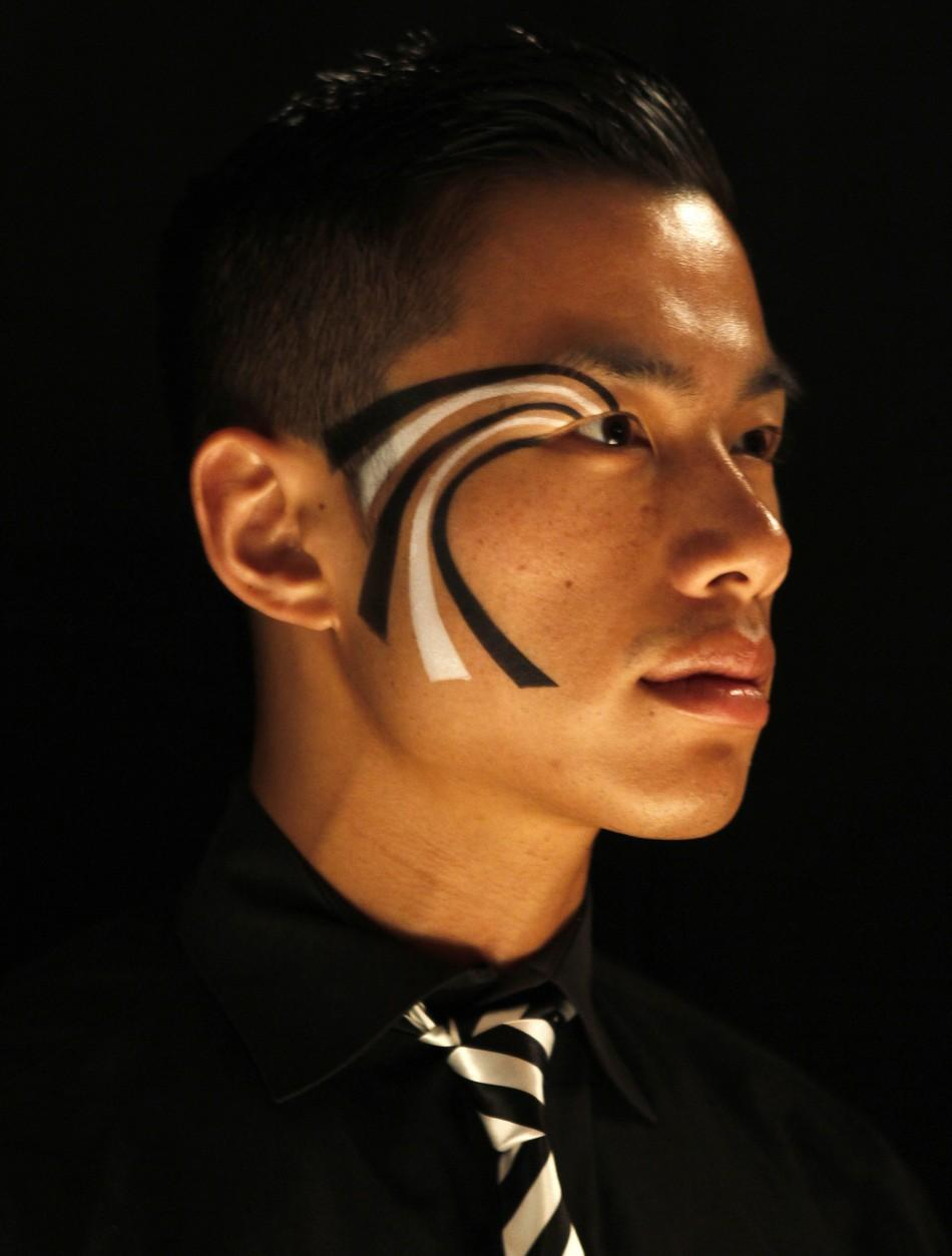 A waiter sports a facial painting featuring the theme, mod illusions, for the 2011 Creative Arts and 63rd Primetime Emmy Awards Governors Ball during a press preview in North Hollywood, California
