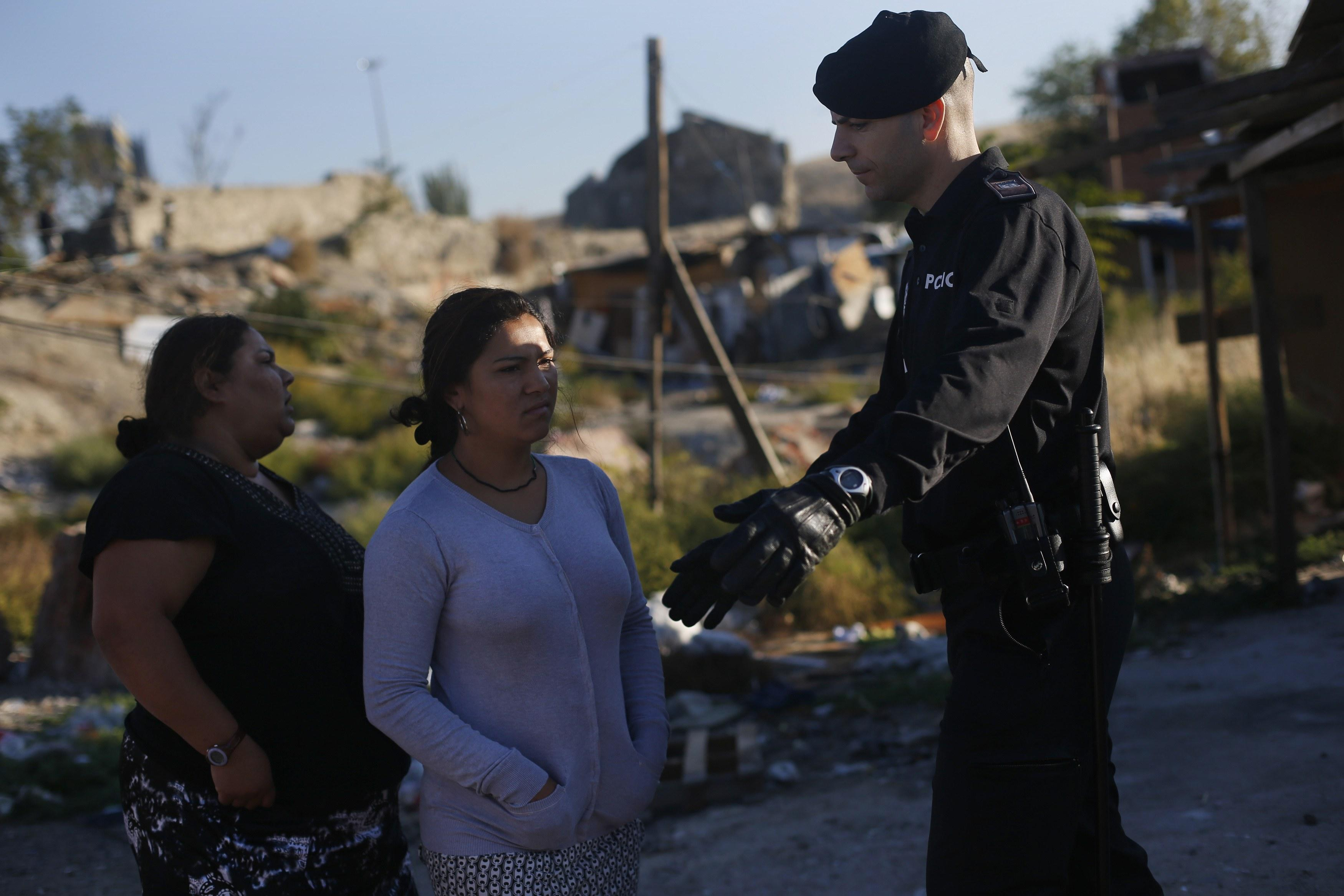 "A woman is blocked from entering her former home, as Spanish police proceeded to demolish it, during an operation in Madrid's ""El Gallinero"" slum."