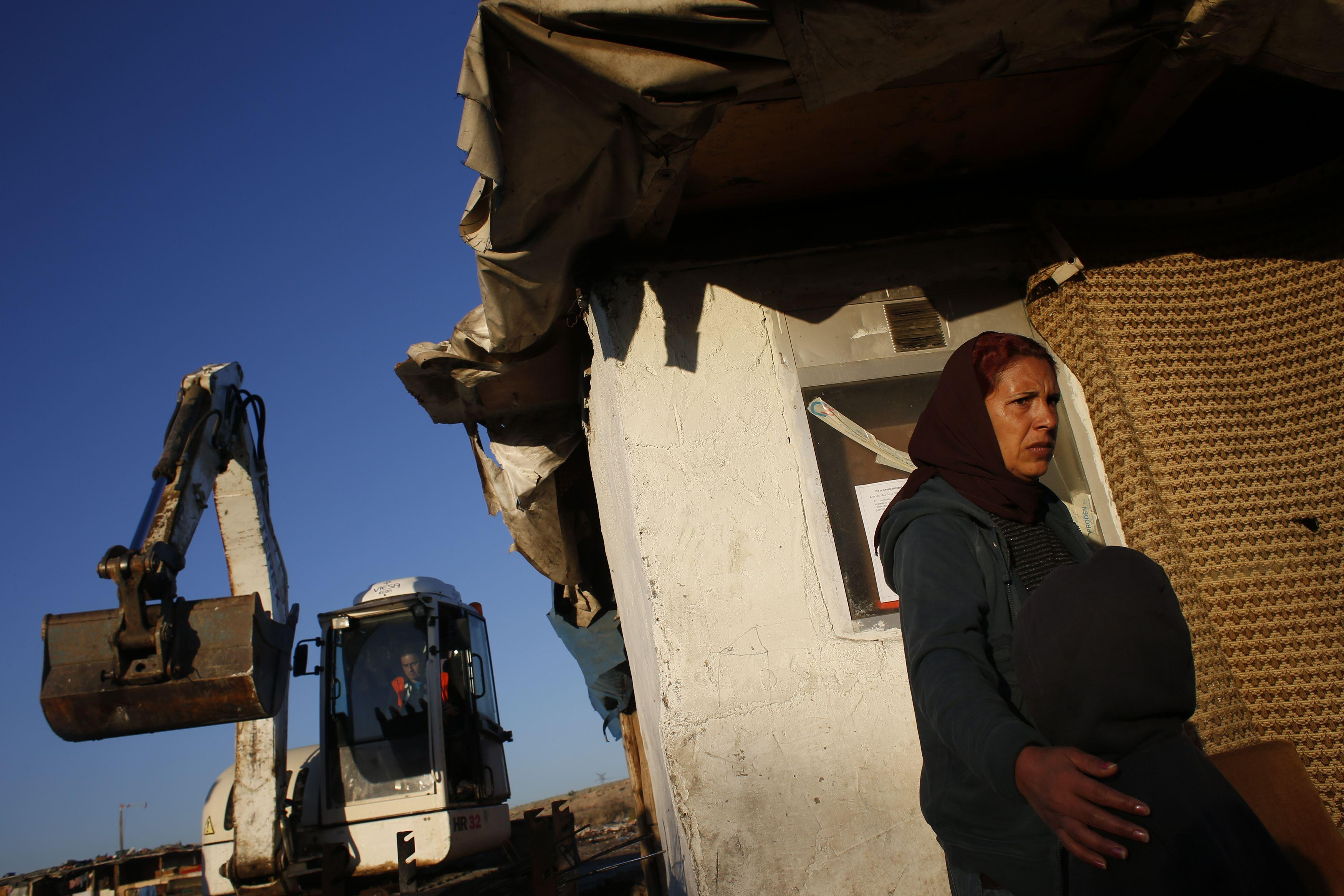 "A woman moves her son away from the path of a bulldozer, as Spanish police proceeded to demolish several homes in her neighborhood, Madrid's notorious ""El Gallinero"" slum."