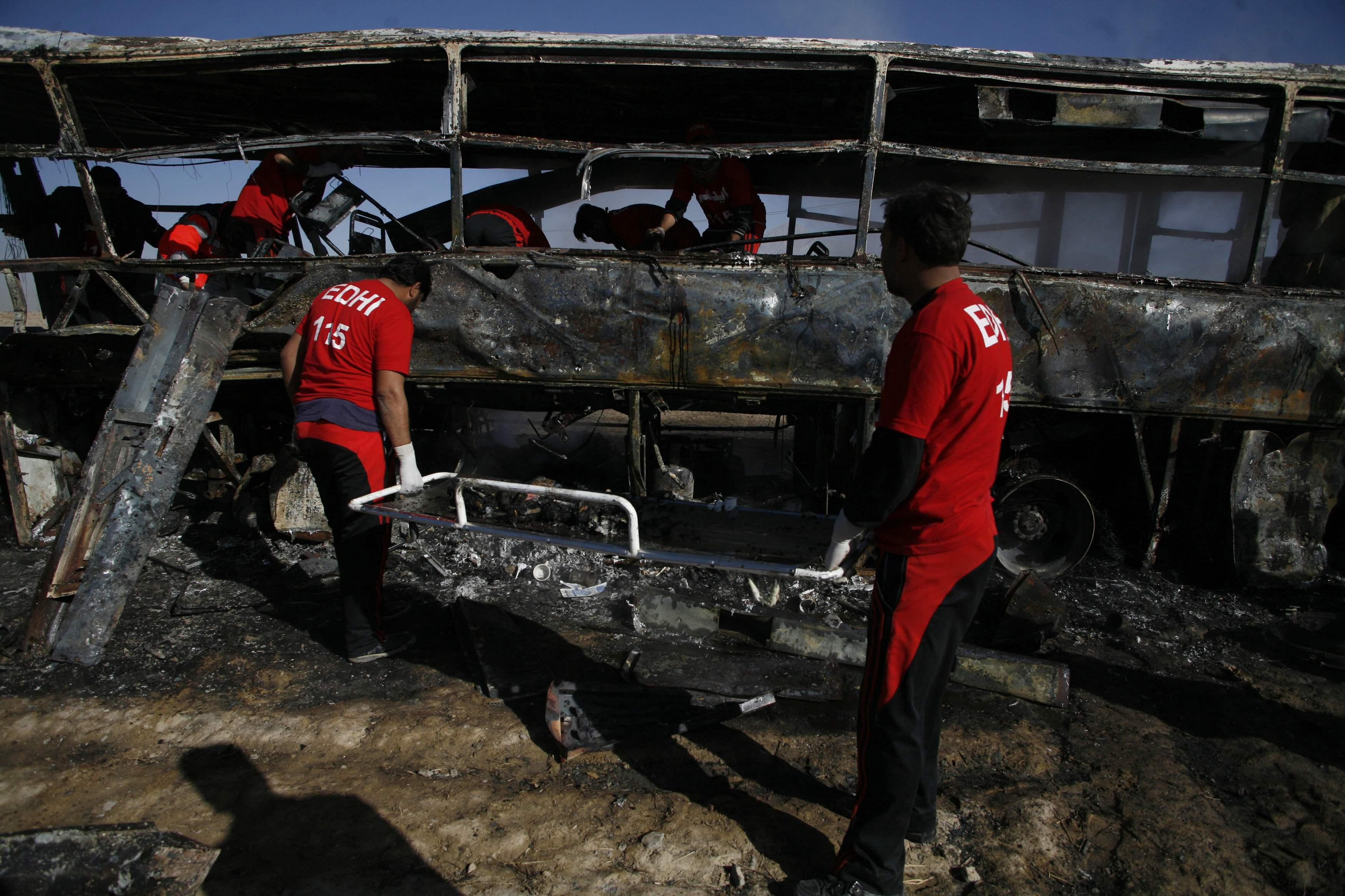 Emergency personnel transport burnt human remains on a stretcher after a car bomb exploded in Quetta