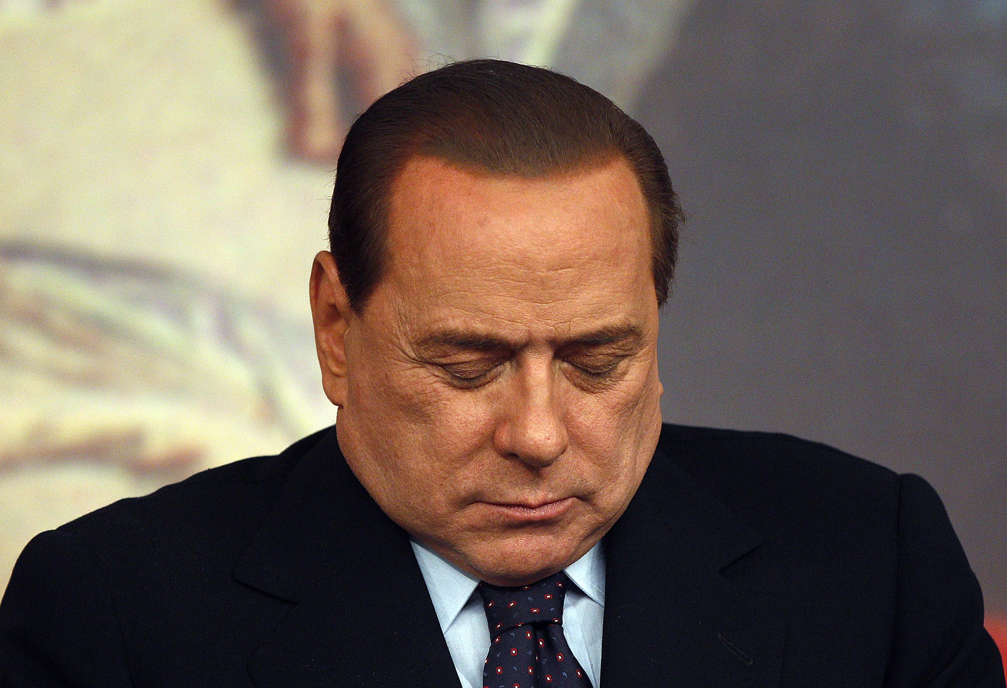 Berlusconi sleeping with head in hands