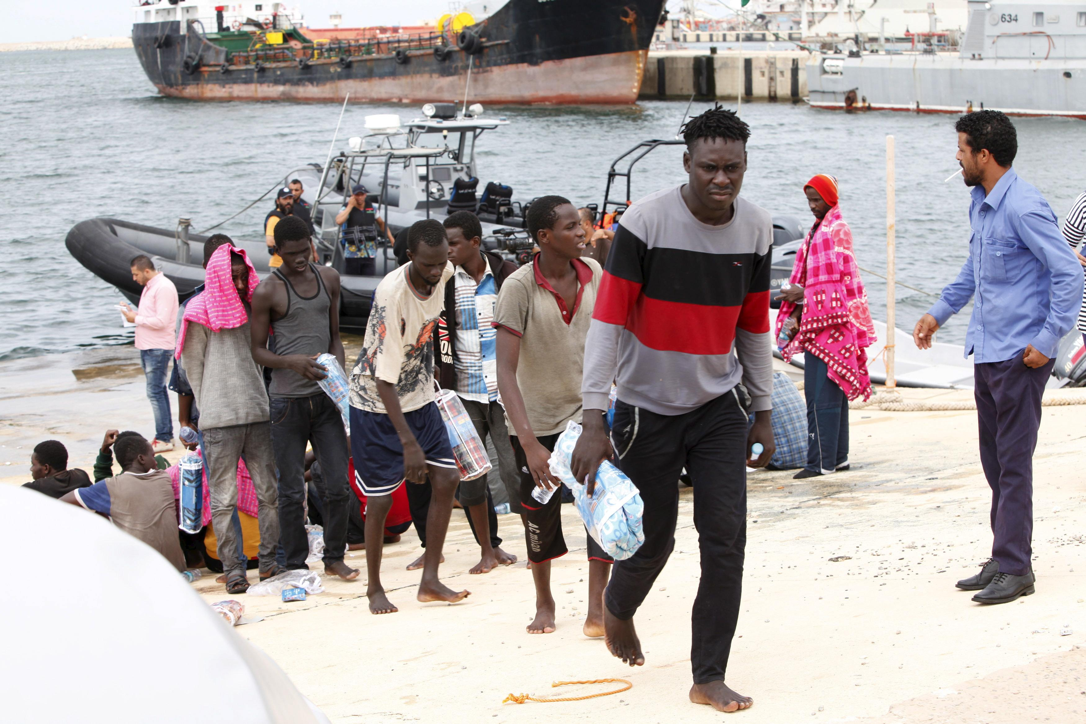 Migrants walk on to the dock in Tripoli.