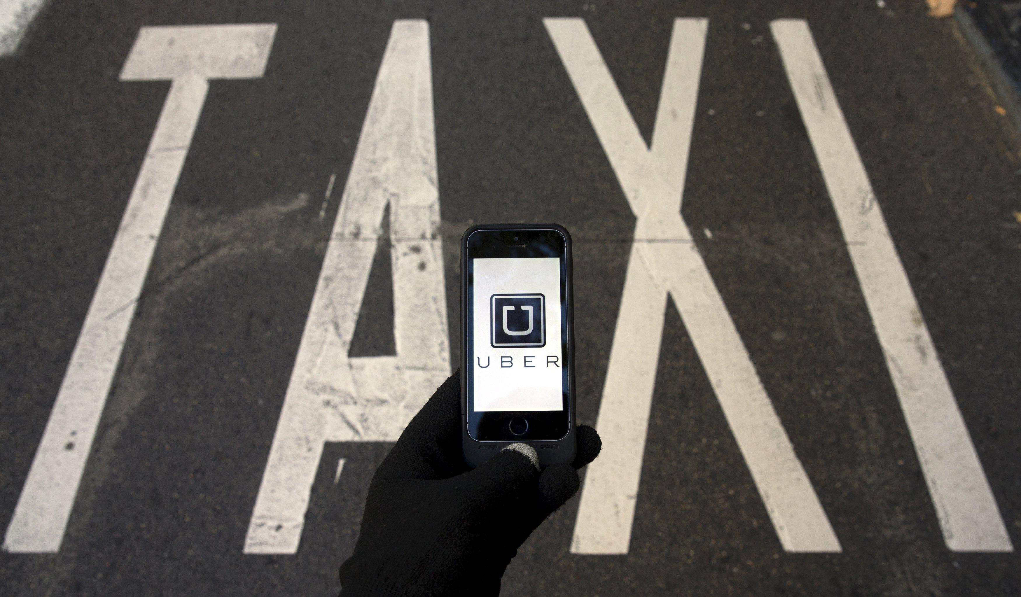 File photo of the logo of car-sharing service app Uber on a smartphone over a reserved lane for taxis in a street in Madrid