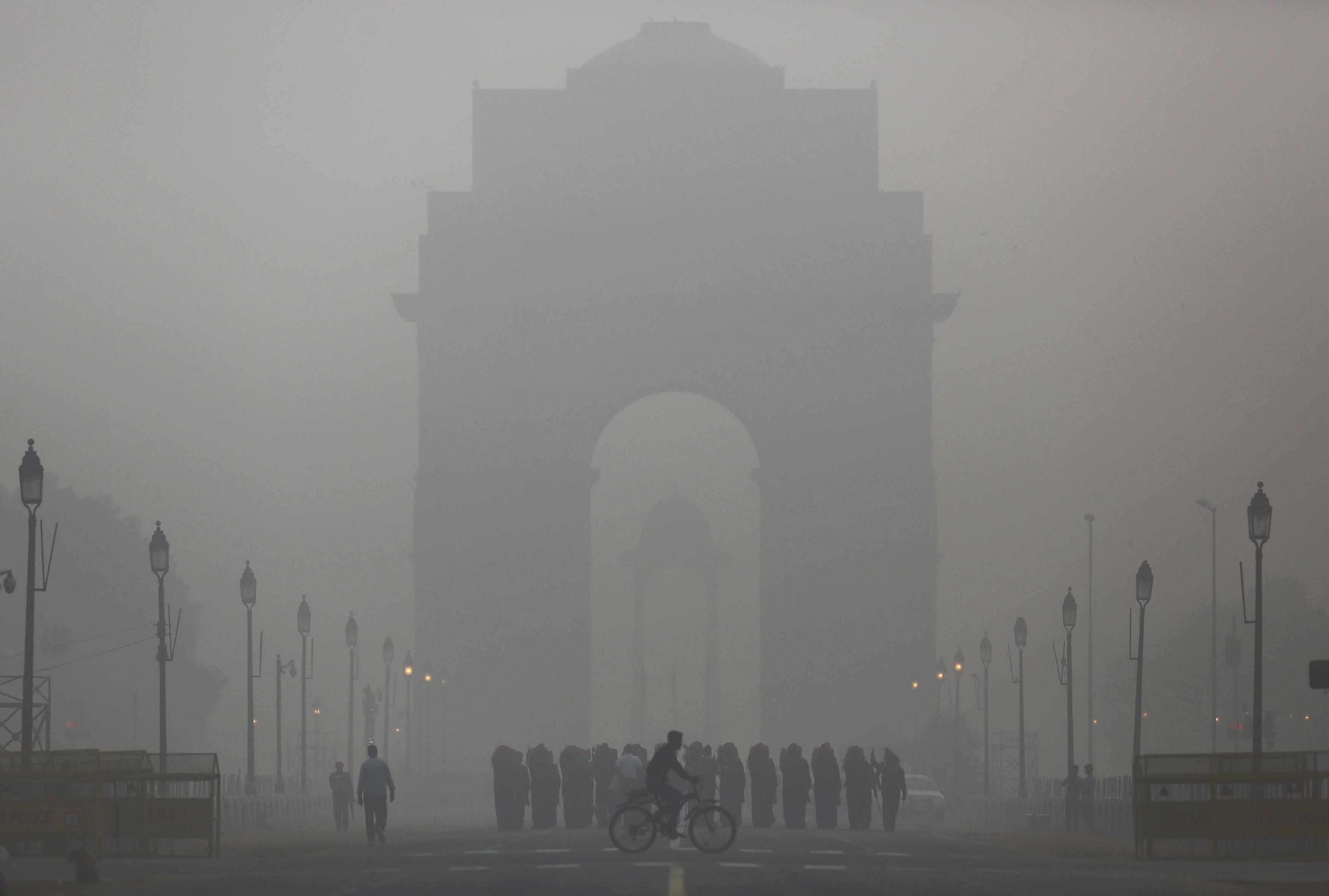 A man rides his bicycle next to Indian soldiers marching in front of India Gate on a smoggy morning in New Delhi, India, December 1, 2015. Photo: Reuters/Anindito Mukherjee