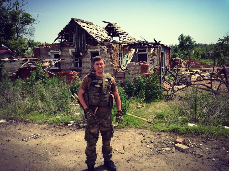 Ivan Rodichenko in front of a bombed out house in Donbass, Ukraine.