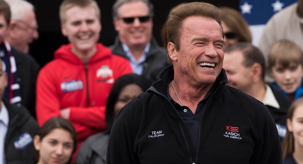 COLUMBUS, OH - MARCH 6: Former California Governor Arnold Schwarzenegger laughs while listening to Ohio Governor John Kasich speak to a crowd during a campaign rally at the Wells Barns at the Franklin Park Conservatory on March 6, 2016 in Columbus, Ohio.