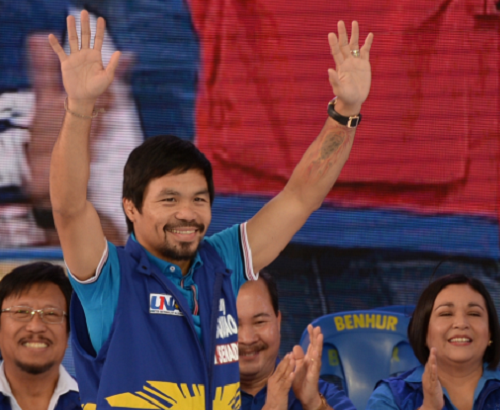 Senatorial candidate of the opposition party and boxing icon Manny Pacquiao greets supporters during his party's proclamation rally in Manila on February 9, 2016.