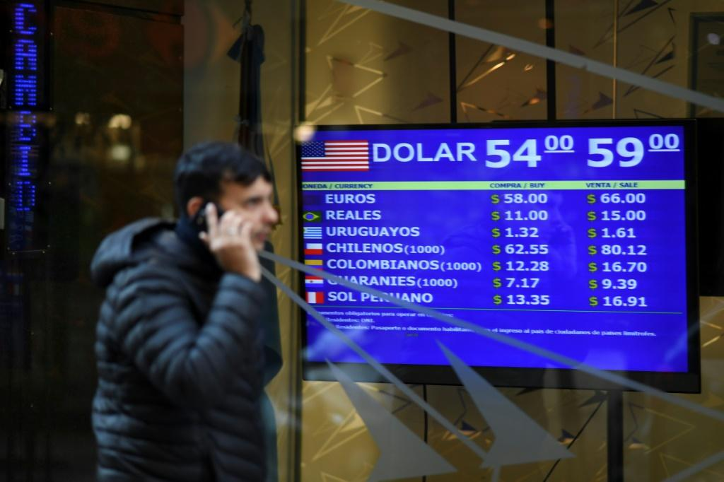 Currency exchange values are displayed on the buy-sell board in Buenos Aires, on August 13, 2019