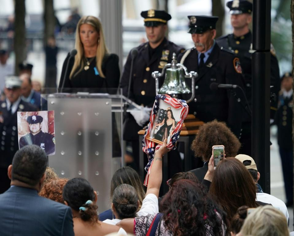 A relative holds the portrait of a victim during the September 11 Commemoration Ceremony at the 9/11 Memorial at the World Trade Center in New York