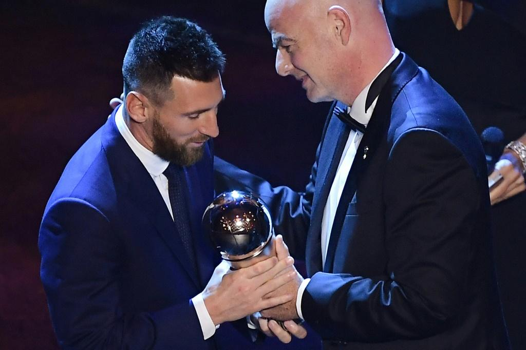 Argentina and Barcelona forward Lionel Messi (L) is presented with the men's player of year award by FIFA President Gianni Infantino.