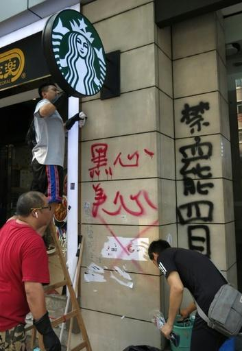 Workers clean graffiti from a Starbucks outlet in Hong Kong after the coffee chain was targetted by protesters because of comments made by the franchise holder's daughter
