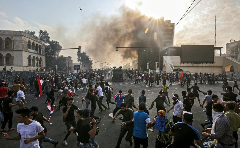 Protesters clash with an Iraqi riot police during a demonstration against state corruption and poor services in Baghdad