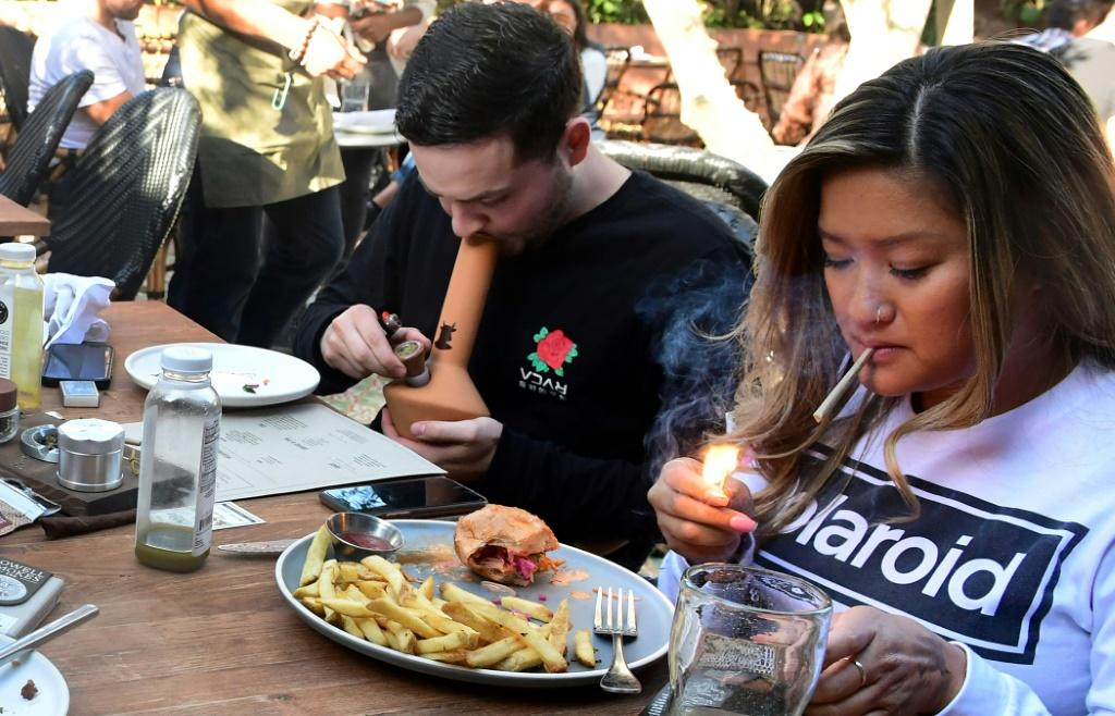 Will Halverson (L) smokes from a bong as Mimi Bui lights a joint with their meal at Lowell Farms: A Cannabis Cafe in West Hollywood, California