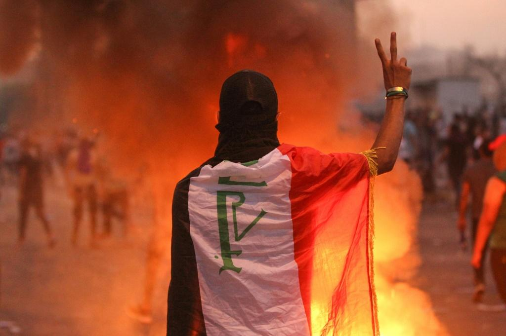 An Iraqi protester gestures the v-sign during a demonstration against state corruption, failing public services and unemployment at a square in Baghdad
