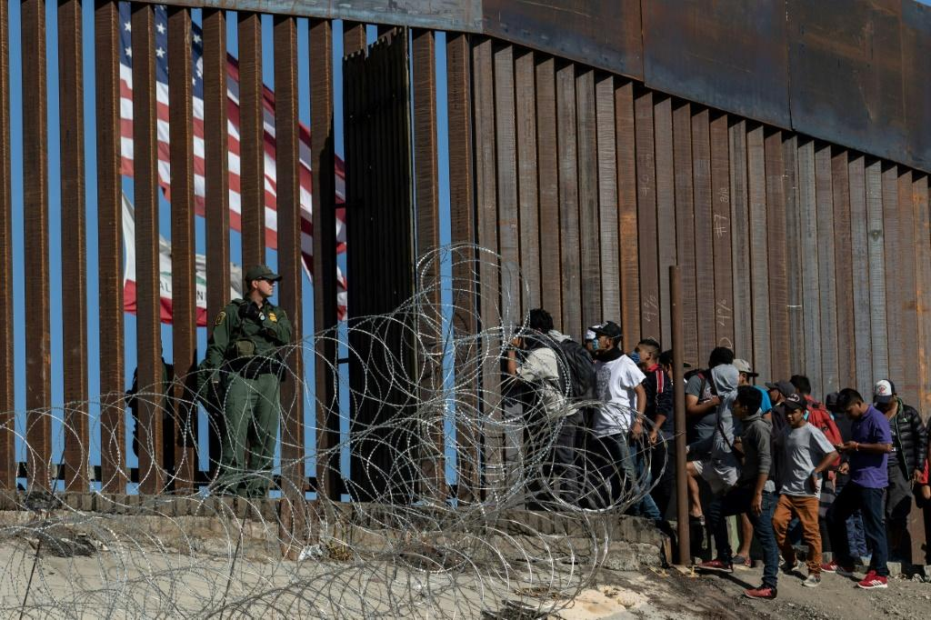 Central American migrants look through a border fence as a US Border Patrol agent stands guard near Tijuana, Mexico: people who cross the border illegally will have their DNA collected by US officials in the future