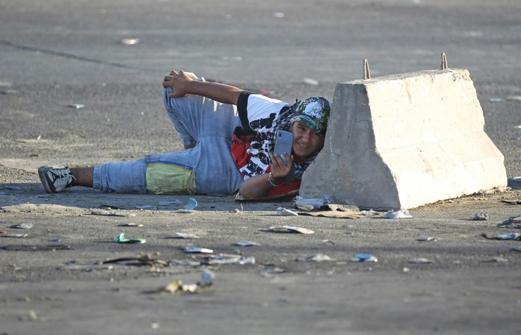 An Iraqi protester takes cover during a protest in central Baghdad on October 4, 2019