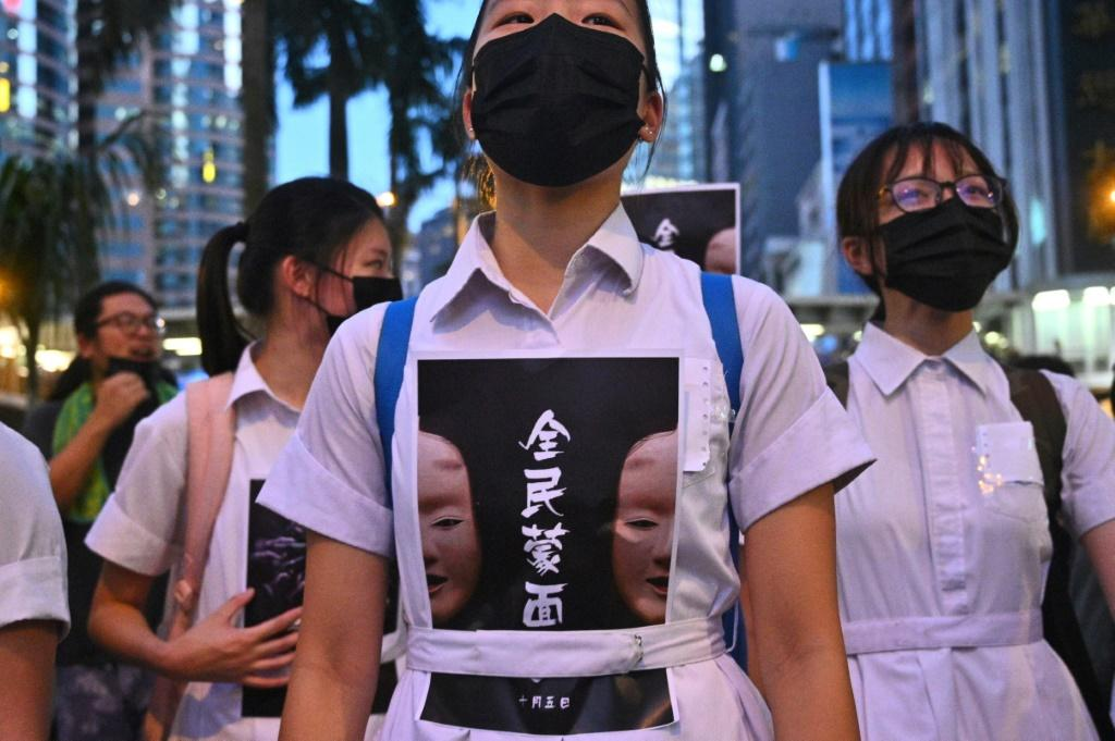 """High school students chanted slogans and stuck posters reading """"all people masked"""" on their uniforms as they gathered in the heart of Hong Kong's commercial district"""