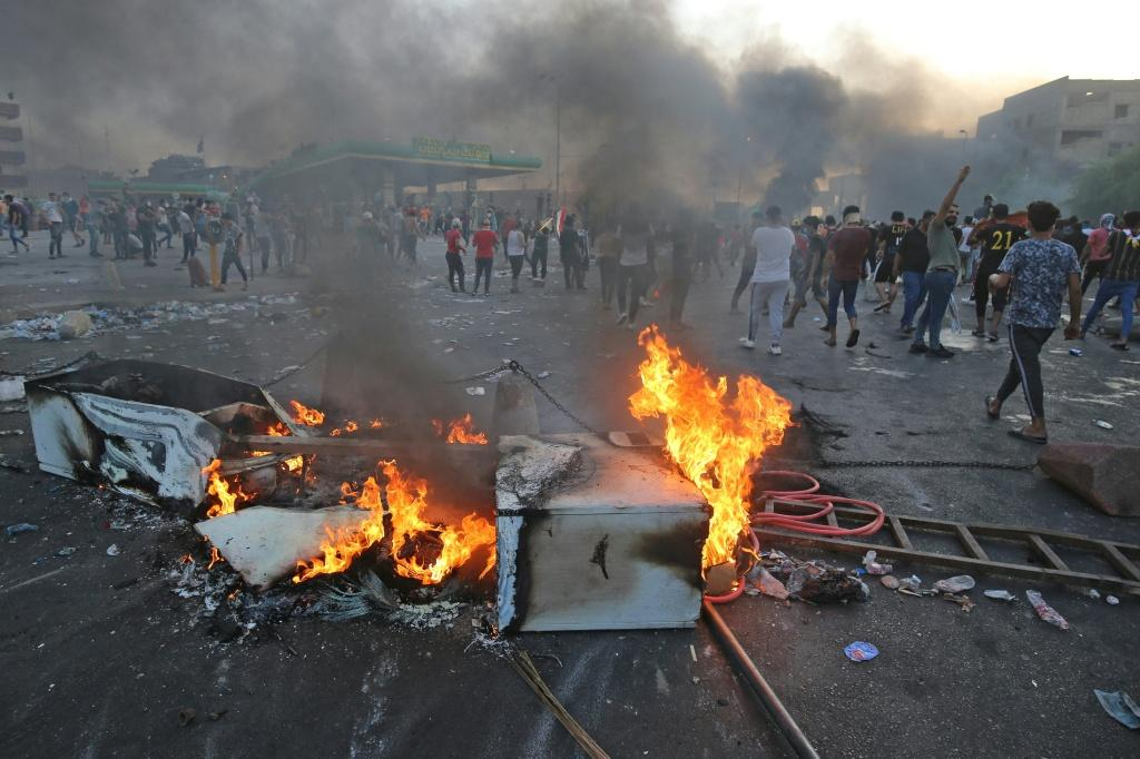 Iraqi protesters burn objects to block the road during clashes amidst demonstrations against state corruption, failing public services, and unemployment in the Iraqi capital