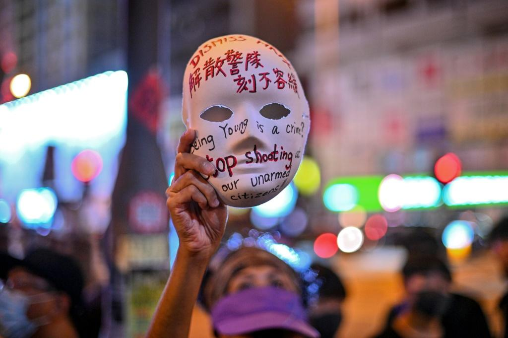 A Hong Kong woman holds a mask with slogans written on it -- critics say the ban on face masks during protests is a major step towards authoritarianism