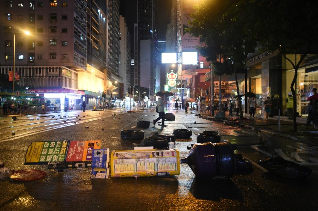A pedestrian (C) walks past debris littering the street after protesters clashed with police in the Wanchai district in Hong Kong