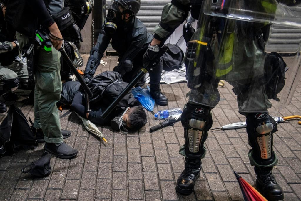 A protester (C) is detained by police during clashes in the Wan Chai district in Hong Kong