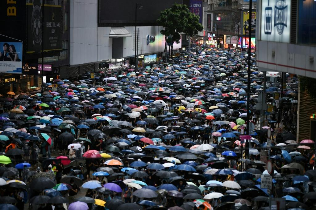 Large crowds marched through torrential rain in unsanctioned rallies on both sides of Victoria Harbour Sunday afternoon.