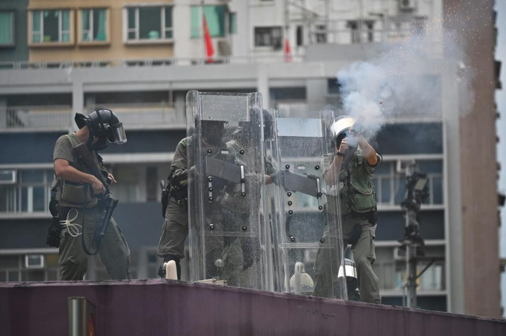 Police fire tear gas from the roof of Mongkok police station toward protesters