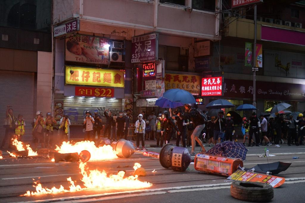 Protesters set fires and battled police Sunday, plunging the finance hub into chaos once more