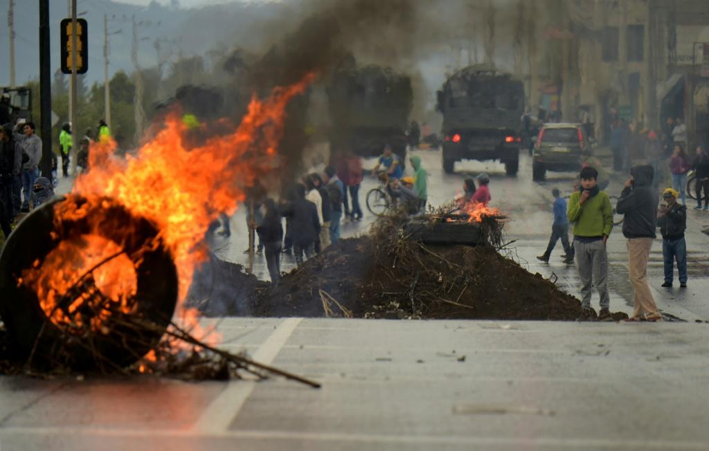 A tire burns at a barricade set by demonstrators in Quito on October 7, 2019 following days of protests against the sharp rise in fuel prices sparked by authorities' decision to scrap subsidies