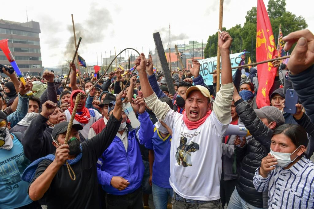 Angry demonstrators shout slogans outside the national assembly in Quito during clashes Tuesday with security forces