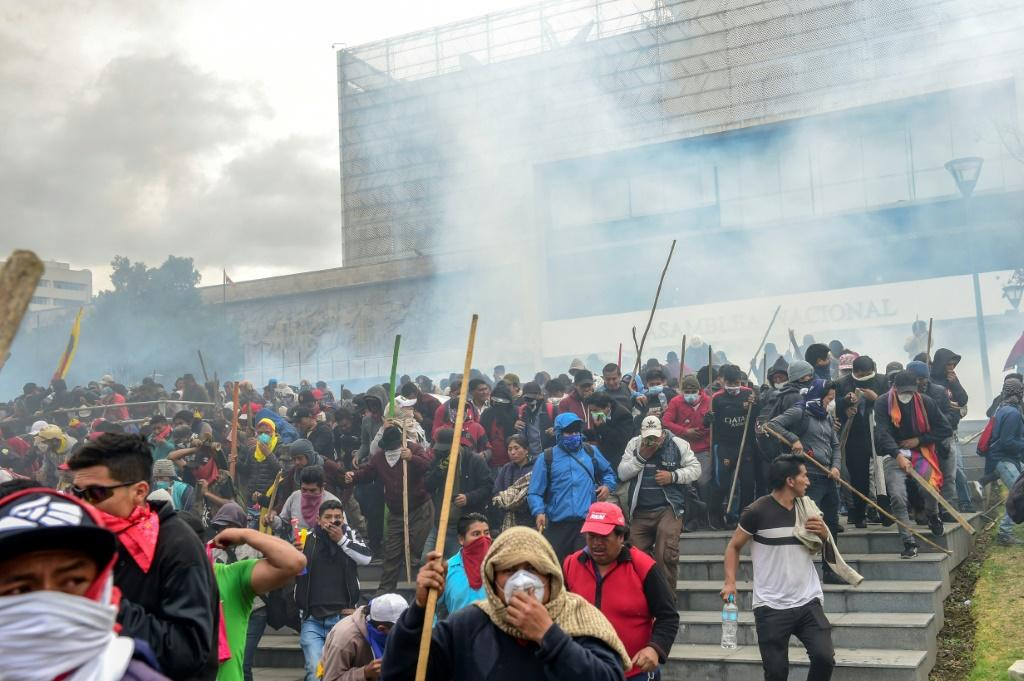 Demonstrators are dispersed away from the national assembly by riot police using tear gas, in Quito on October 8, 2019
