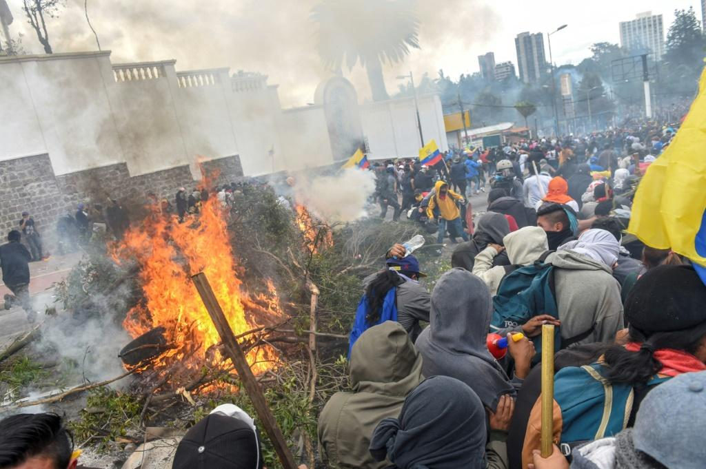 Demonstrators burn branches and tyres outside the national assembly in Quito during clashes with security forces on October 8, 2019