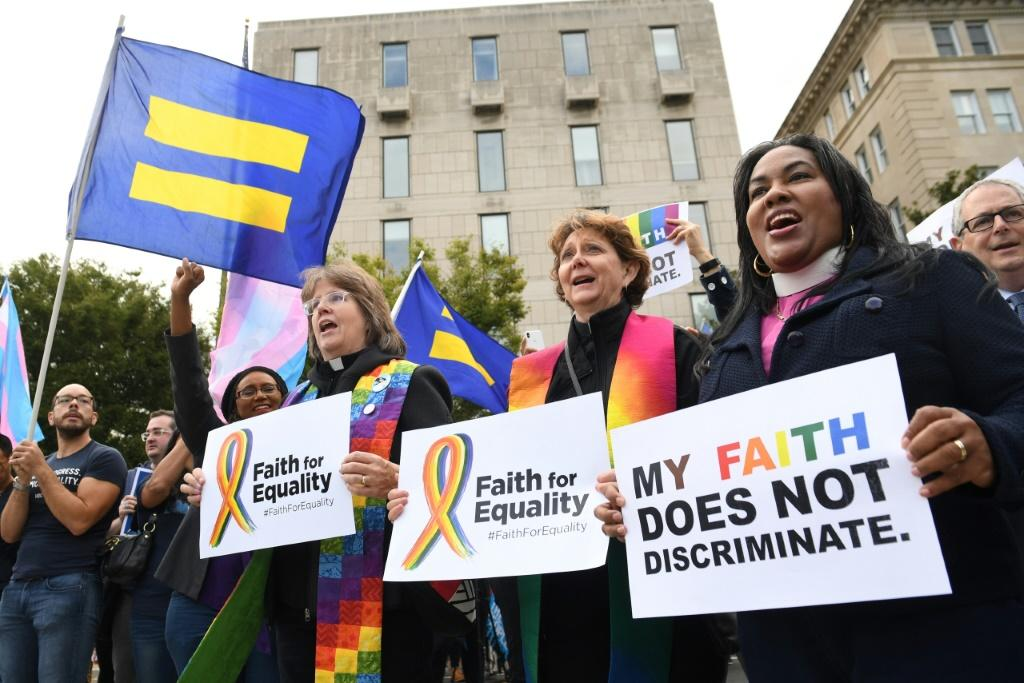Demonstrators in favor of LGBT rights rally outside the US Supreme Court in Washington ahead of the court's hearing on gay and transgender workplace rights