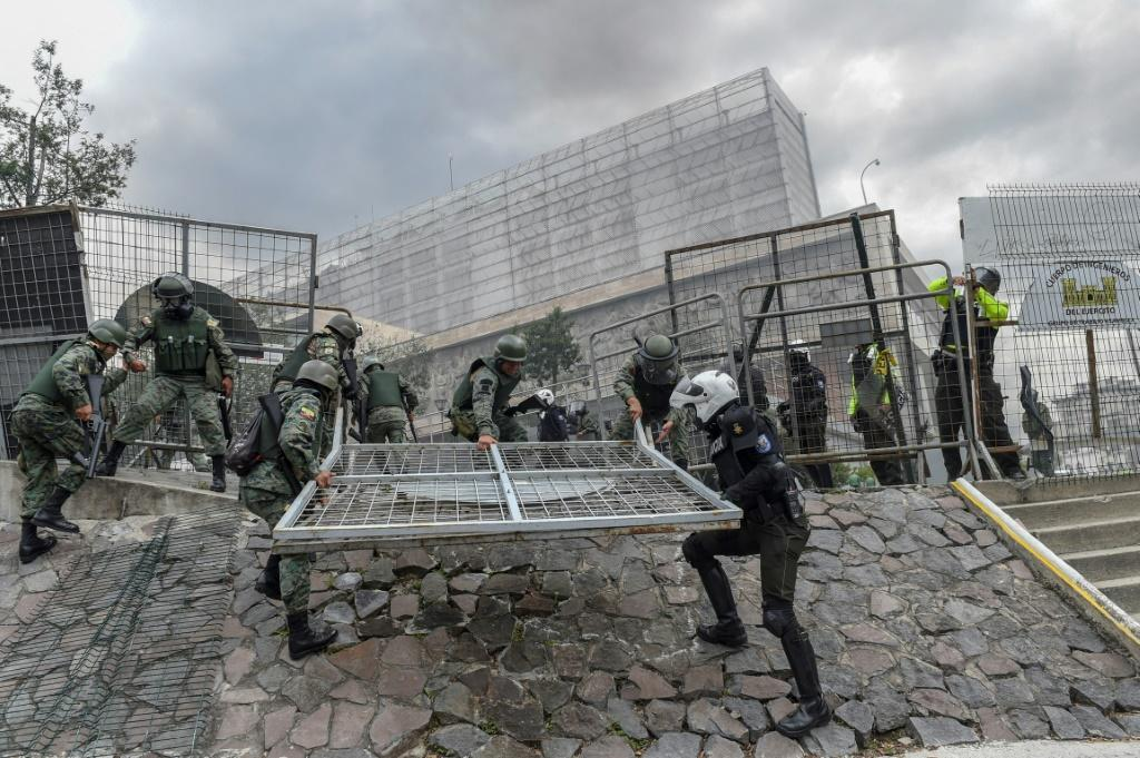Security forces rush to erect a metal fence during clashes with demonstrators near the national assembly in Quito