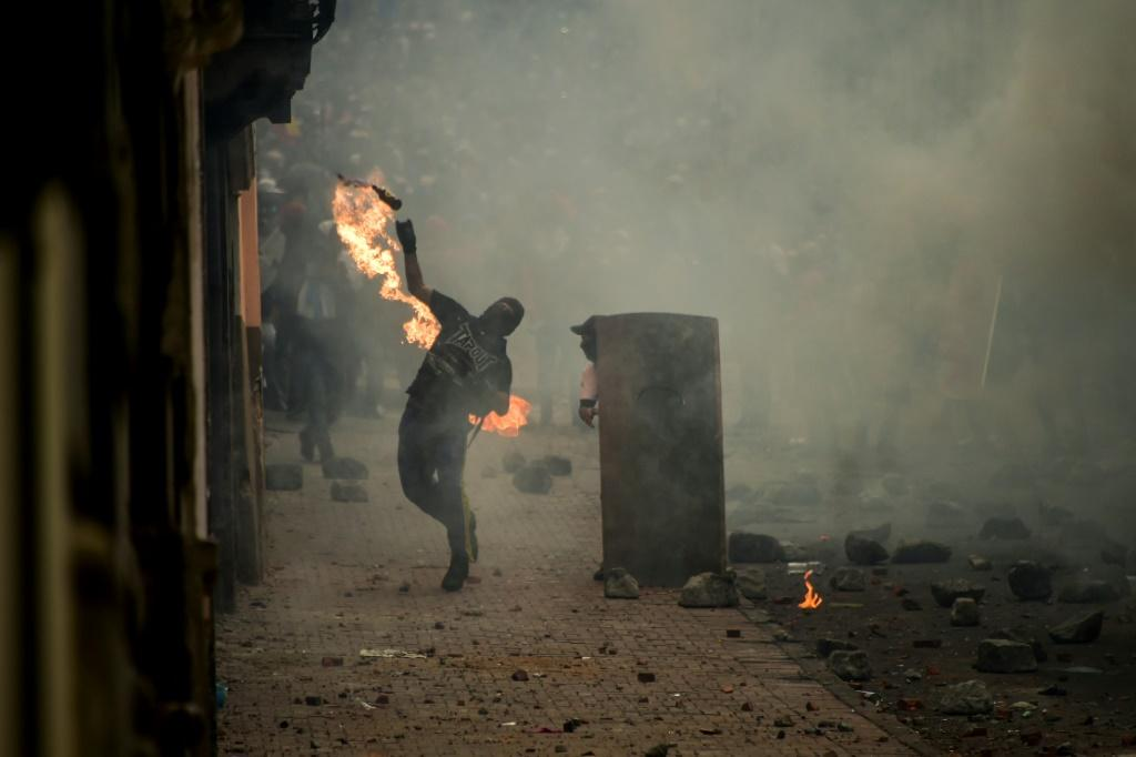 A demonstrator throws a Molotov cocktail at riot police during clashes in Quito