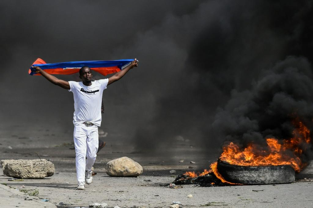 A demonstrator waves a Haitian flag during a protest against President Jovenel Moise on October 4, 2019 in Port-au-Prince