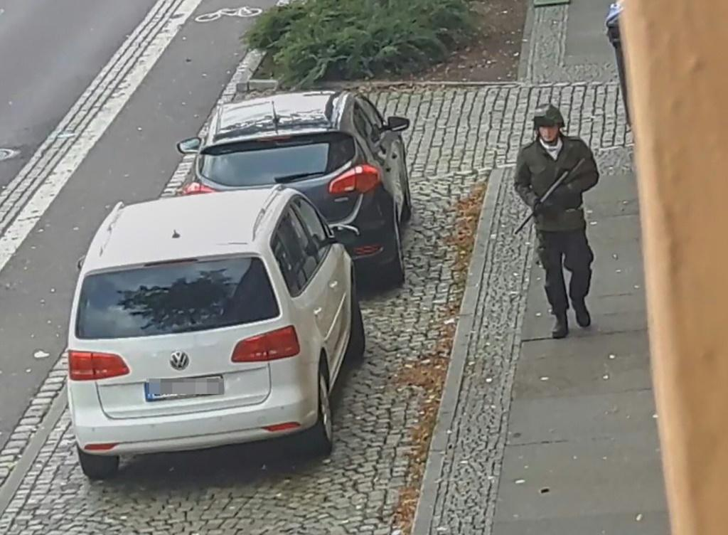 A screenshot taken from a video by ATV-Studio Halle shows a man walking with a gun in the streets of Halle