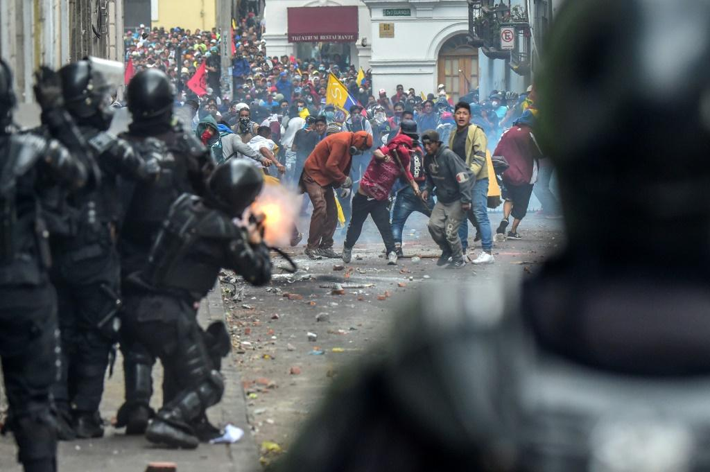 Demonstrators clash with riot police as thousands march against Ecuadorean President Lenin Moreno's decision to slash fuel subsidies, in Quito on October 9, 2019