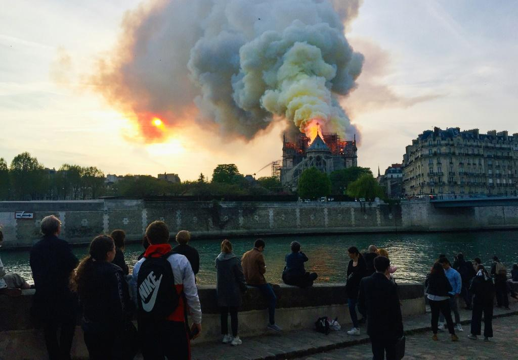 Bystanders look on as flames and smoke billow from the roof of Notre-Dame
