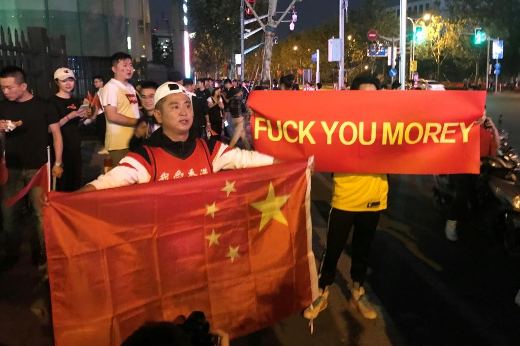 Outside the game venue, a pair of protesters held up red banners