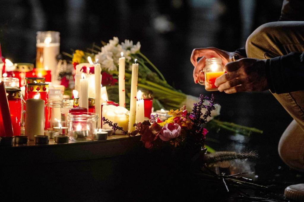 People leave candles and flowers at a vigil at the Marktplatz in Halle, eastern Germany