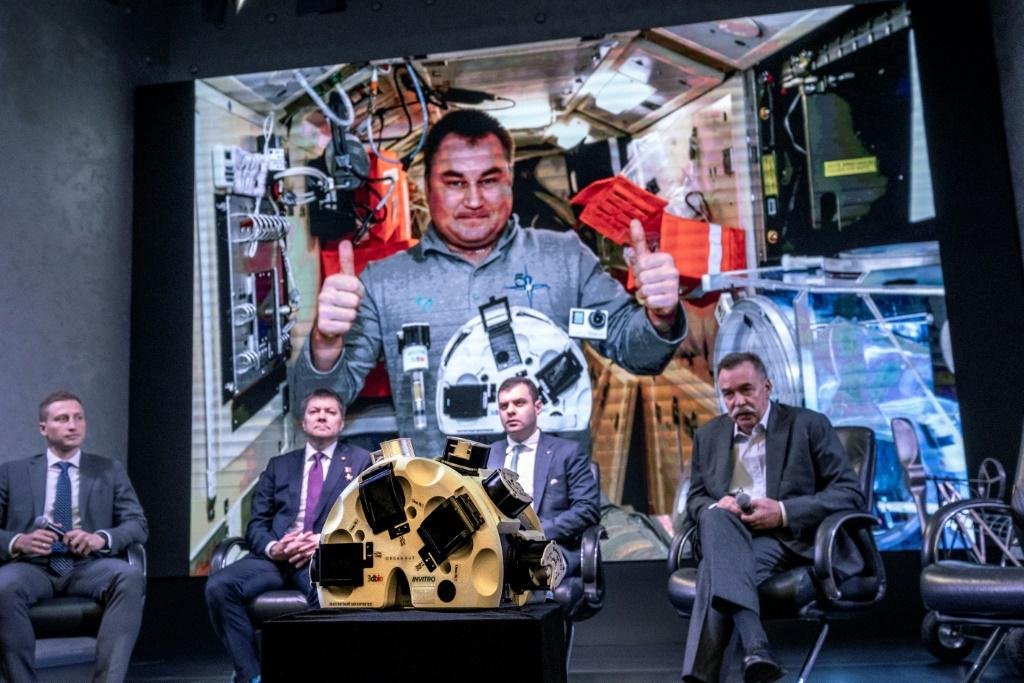 Russian cosmonaut Oleg Skripochka (on screen) poses in the International Space Station with a 3D bioprinter that created beef, rabbit and fish tissue from cells using magnetic fields in microgravity