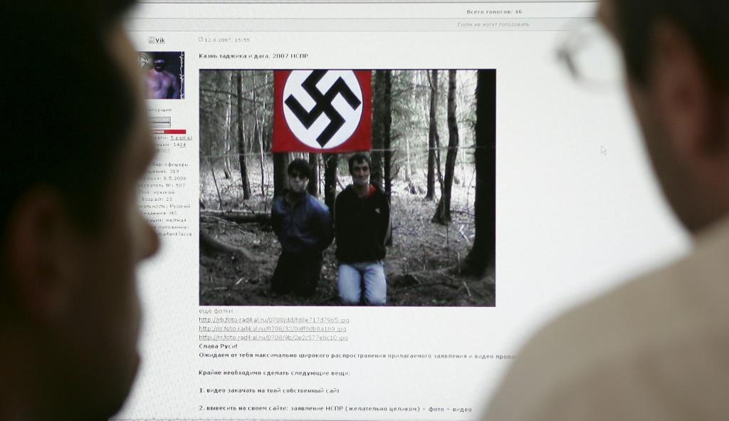 Two men look at the website of the United Slavic National-Socialists Forum on a computer in Moscow in 2007 which contained a video apparently executing a Tadjik national and an ethnic Dagestani man in a forest with a Nazi flag in the background.